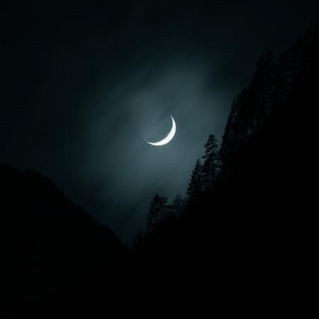 Luna que reluce entre montañas de noche